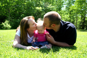 Young family together, kissing baby